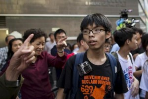 Student leader Joshua Wong is scolded by government supporters (L) during a promotional event on electoral reform in Hong Kong, China April 25, 2015. REUTERS/Tyrone Siu