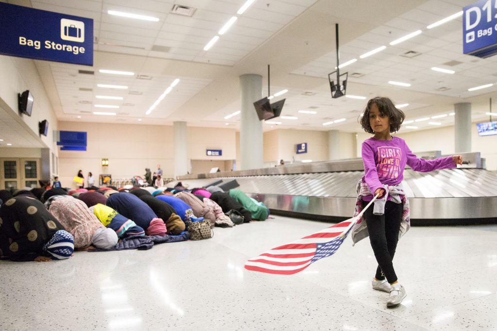 A young girl dances with an American flag while women pray behind her during a protest against the temporary travel ban