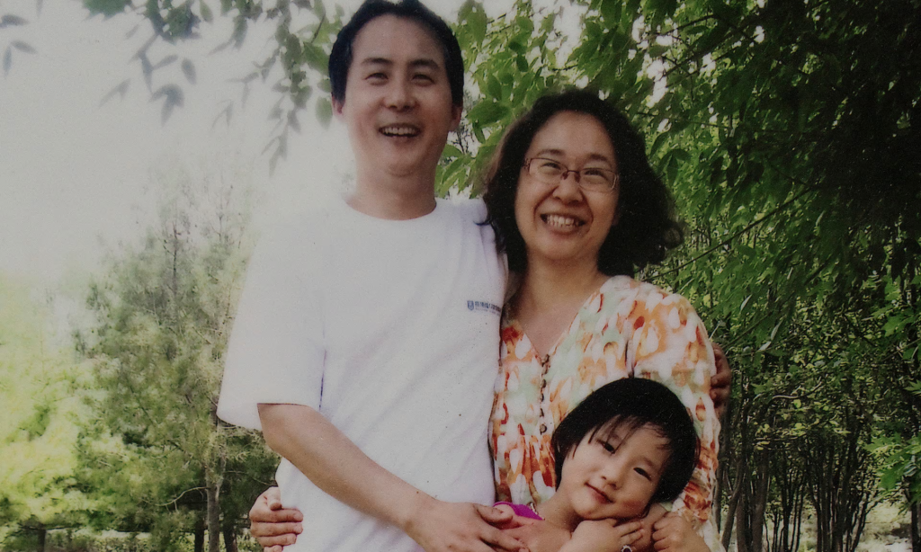 A photo of a printed family photo of Li Jiamei-her father and imprisoned lawyer Li Heping and her mother Wang Qiaoling at home in Beijing