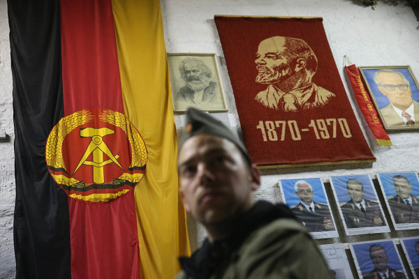 SUHL, GERMANY - OCTOBER 17: A visitor dressed as an East German NVA army soldier looks at memorabilia of the former communist East Germany (DDR), including the East German flag and portraits of Karl Marx, Vladimir Lenin and Erich Honecker, during an overnight stay in the Bunkermuseum Frauenwald on October 17, 2014 near Suhl, Germany. The bunker was built by the East German secret police (Ministry for State Security, or Ministerium fuer Staatssicherheit, also called the Stasi) in the 1970s and was one of at least 15 similar bunkers meant to serve as command and administrative centers in case of war. The bunker could house up to 130 people in its 3600 square meter facility, which had supplies for three weeks and decontamination systems against chemical attack. Today the bunker is a private museum that offers tours and overnight stays in which visitors are given the option of dressing as East German army soldiers for a more authentic experience. Germany is commemorating the 25th anniversary of the fall of the Berlin Wall, which signalled the collapse of communist East Germany (also called the DDR, or Deutsche Demokratische Republik) in 1989, in November of this year. (Photo by Sean Gallup/Getty Images)