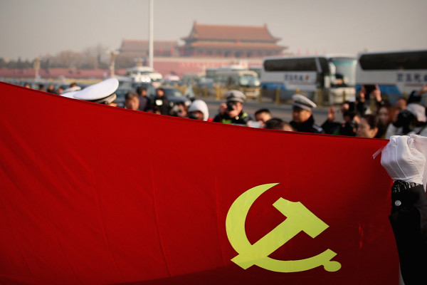 BEIJING, CHINA - MARCH 05: Policemen holding the flag of China's Communist Party pose for photos during the opening session of the National People's Congress at the Tiananmen Square on March 5, 2015 in Beijing, China. The government work report presented the main targets of economic and social development, a projected 2015 GDP growth of about 7 percent; and consumer prices rising about 3 percent. (Photo by Feng Li/Getty Images)