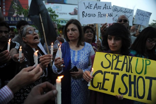 Activists of Human Rights Commission of Pakistan (HRCP) hold candles and placards as they shout slogans during a protest against the killing of Pakistani lawyer Rashid Rehman in Islamabad on May 8, 2014. Lawyers in the central Pakistani city of Multan went on strike to mourn a colleague who was shot dead for defending a university lecturer accused of blasphemy. Gunmen stormed the office of lawyer Rashid Rehman on May 7 evening and started firing indiscriminately, killing him and injuring two others. AFP PHOTO/Aamir QURESHI / AFP / AAMIR QURESHI