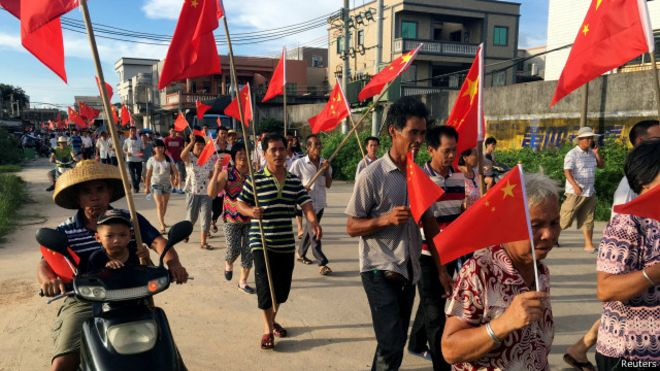 乌坎村民在黄昏前聚集在一起,他们举着红旗,喊要求释放村委主任林祖恋的口号。