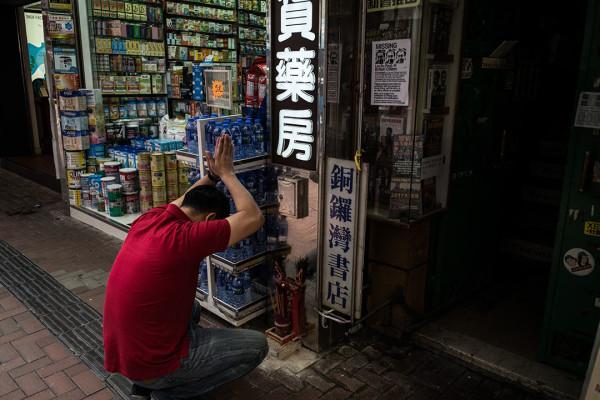 一名药房员工在铜锣湾书店入口旁拜神