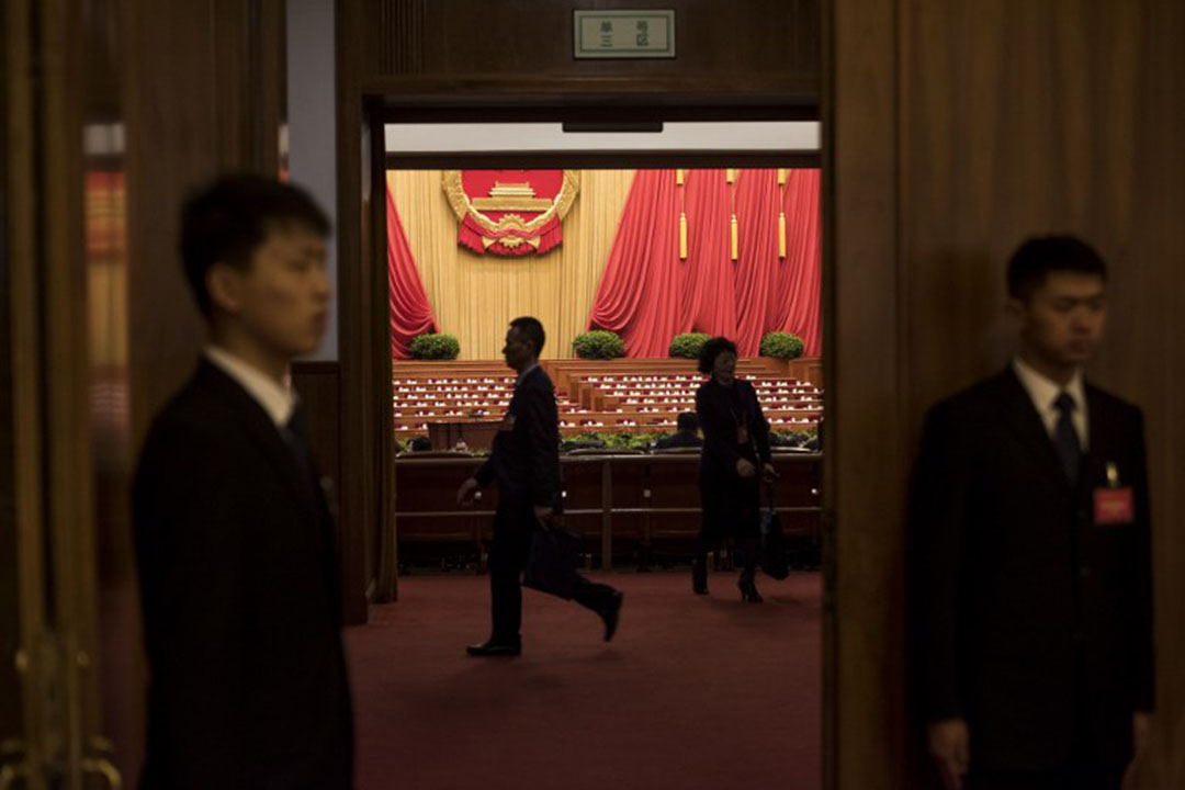 Security guards check an the entrance during the third plenary session of the National People's Congress at the Great Hall of the People in Beijing on March 13, 2016. China's leaders are meeting this week for the annual rubber-stamp National People's Congress, where Premier Li Keqiang set a growth target of 6.5-7.0 percent for this year. / AFP PHOTO / FRED DUFOUR