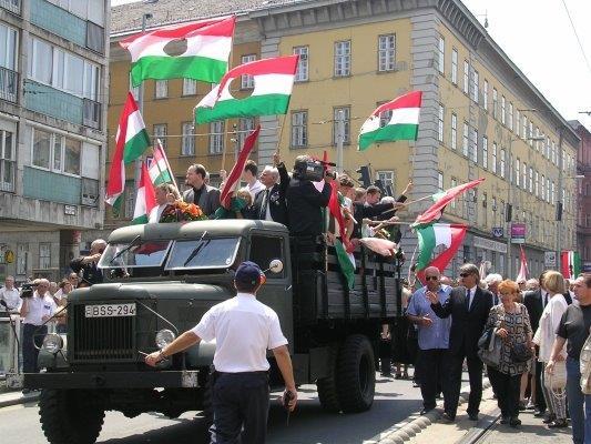 布达佩斯的学生和市民高举着挖掉共产党纹章的国旗游行