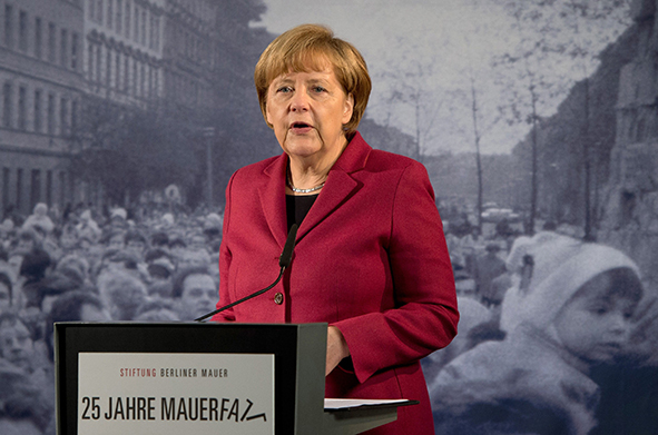 German Chancellor Angela Merkel delivers her speech in front of a giant reproduction of a photo dated from November 1989 as she opens an exhibition dedicated to the Berlin Wall during commemorations to mark the 25th anniversary of the fall of the Berlin Wall at the Berlin Wall Memorial in the Bernauer Strasse in Berlin, on November 9, 2014.   AFP PHOTO / DPA / SOEREN STACHE