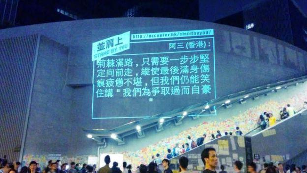 """""""打气小队""""在""""雨伞运动""""期间,把世界各地的打气讯息投影在政总外墙"""