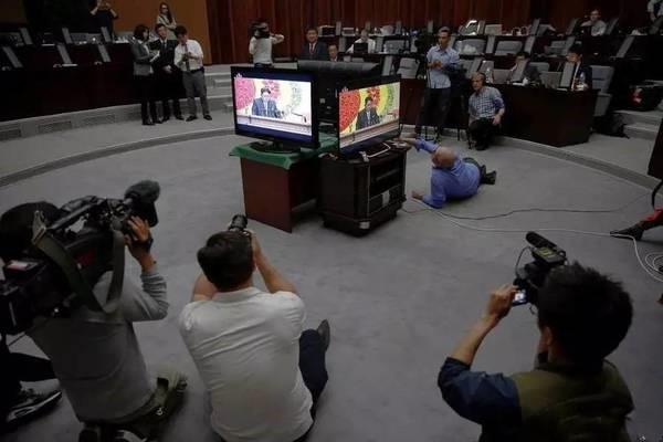 外媒记者们在一个房间里对着四个电视机拍摄