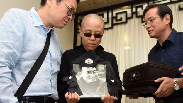 官方发布的图片中可见,刘霞在告别式上捧着刘晓波的遗像。