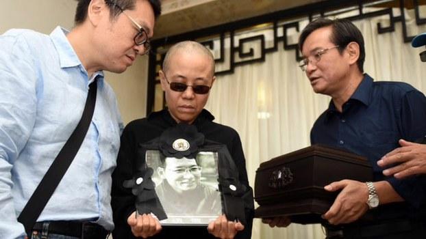 刘晓波妻子刘霞(中)接过丈夫照片后,紧紧抱在怀中,神情哀伤,其弟刘晖(左)在旁掺扶,刘晓波弟弟刘晓暄(右)则捧著骨灰