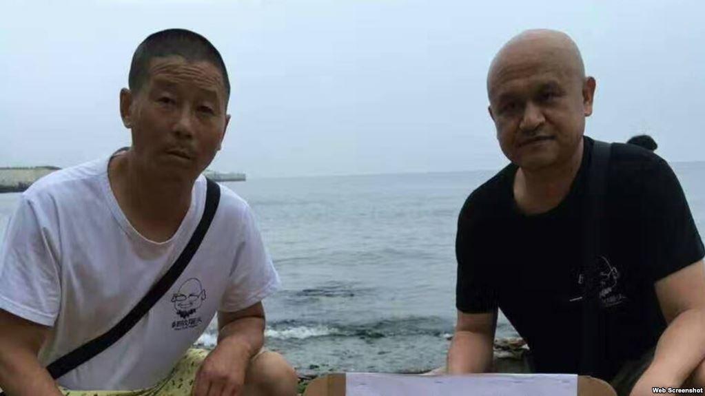 姜建军(左)、王承刚在大连老虎滩海边祭奠两天前海葬于附近海域的刘晓波