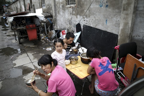 epa06110119 People have lunch outside a rental house located in a demolition area in rural Beijing's Changping district, China, 26 July 2017. Several hundred migrant workers living in their temporary houses have to move out as local government begins to demolish the area following the capital's new urban planning policy. Beijing's new mayor Cai Qi has vowed to cut the city off all the functions unrelated to its status of national capital, in an effort to push the growing population into the surrounding provinces and to tear down wholesale markets and urban villages where the migrants work and live, in an attempt to force lower-income residents out of the city.  EPA/WU HONG