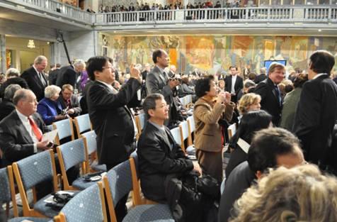 刘晓波诺贝尔颁奖会场。中坐戴眼镜者阿木,前站拍照者齐家贞