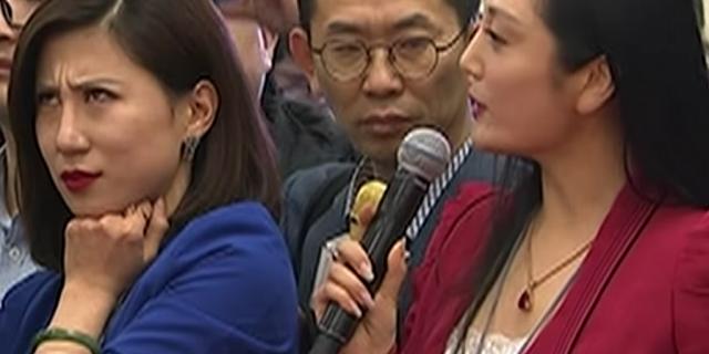 翻白眼事件中的两位女记者,穿蓝衣的是梁相宜,穿红衣的是张慧君。