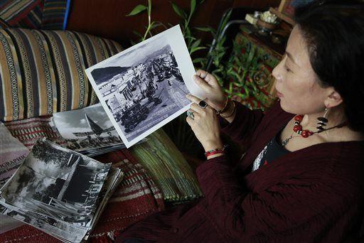 唯色正向美联社记者介绍父亲拍摄的西藏文革照片