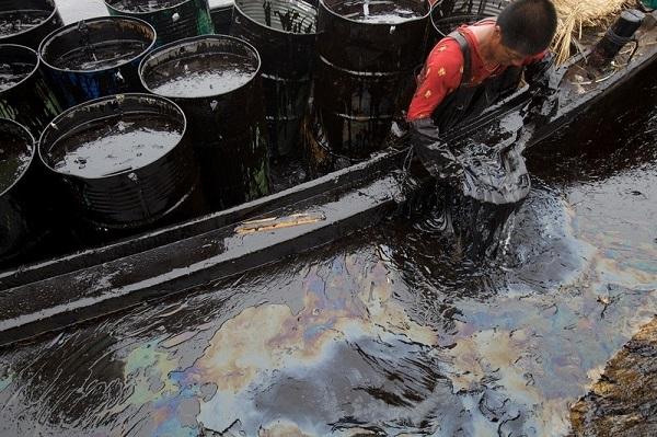 当地渔民在缺乏防护服的情况下清理油污